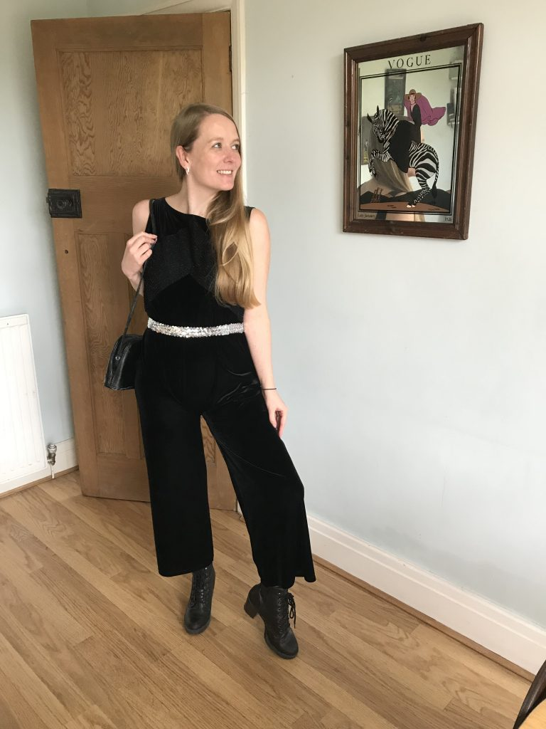 Woman poses in black jumpsuit with silver sequin waistband